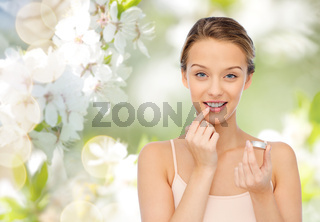 smiling young woman applying lip balm to her lips