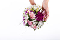 Hands holding a pastel bouquet from pink and purple gillyflowers and alstroemeria on white