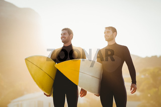 Two men in wetsuits with a surfboard on a sunny day