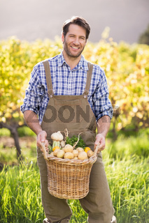 Smiling farmer holding a basket of potatoes