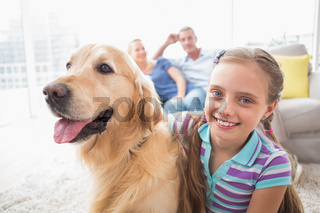 Girl with dog while parents relaxing at home