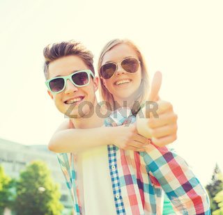 smiling couple having fun and showing thumbs up