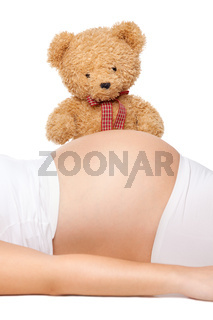 Cute teddy bear looking at belly of a pregnant woman