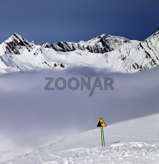 Warning sing on off-piste slope and mountains in fog