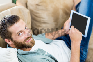 Portrait of man lying n sofa and using digital tablet