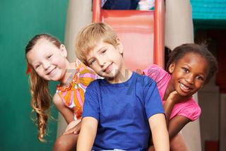 Lachende Kinder auf Rutsche im Kindergarten