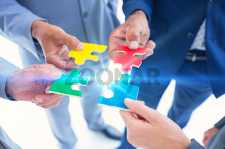 Business colleagues holding piece of puzzle