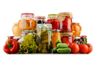 Jars with pickled vegetables and fruity compotes isolated on white background. Preserved food