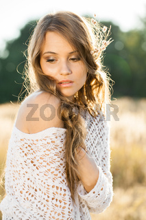 Portrait of a beautiful young lady model in open field