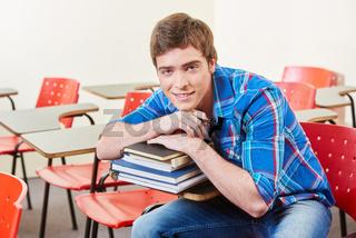 Schüler stützt sich auf Stapel Bücher