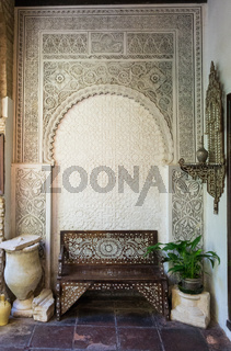 Ornate bench and archway in courtyard in Cordoba Spain