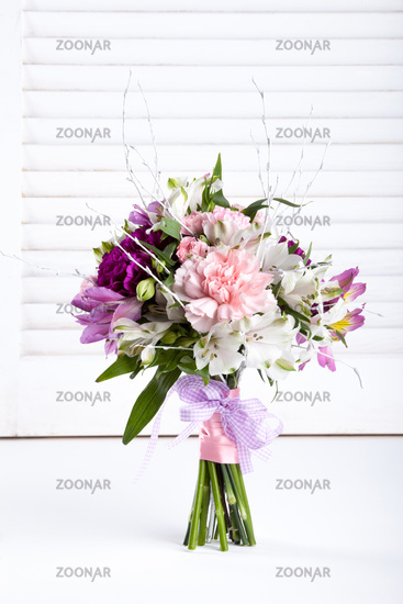 Pastel bouquet from pink and purple gillyflowers on white shutters