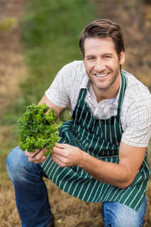 Young happy farmer looking at camera while holding vegetable
