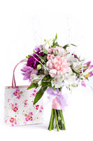 Pastel bouquet from pink and purple gillyflowers on white with gift