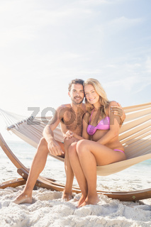 Smiling couple sitting in hammock