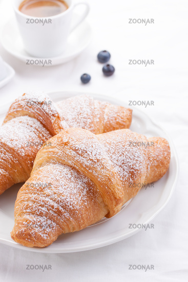 Couple of croissants on a white plate with coffee and berries