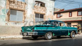 Grüner amerikanischer Oldtimer auf der Landstrasse im Landesinneren von Kuba Santa Clara