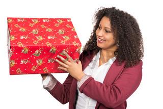 Frau schaut auf ein Weihnachtsgeschenk