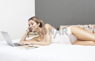 Young sensual latin woman relaxing in bed with laptop