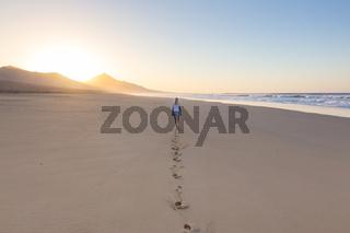 Lady walking on sandy beach in sunset leaving footprints behind.