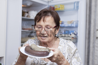 Happy senior woman holding plate with pork liver sausages