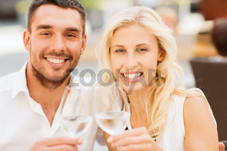 happy couple clinking glasses at restaurant lounge
