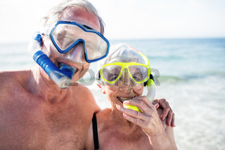 Happy senior couple with their diving mask at beach