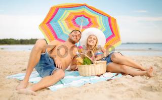 couple having picnic and sunbathing on beach