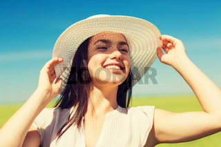 smiling young woman in straw hat outdoors
