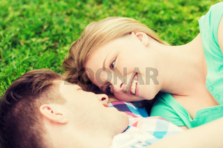 smiling couple lying on grass in park