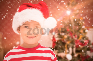 Composite image of cute little boy in santa hat