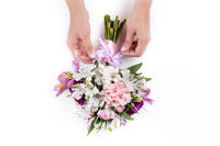 Making a ribbon on pink bouquet from gillyflowers and alstroemeria on white