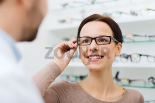 woman choosing glasses at optics store