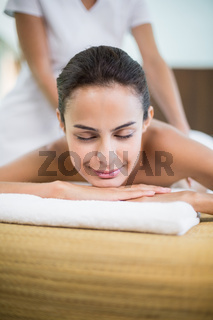 Woman with eyes closed while receiving massage