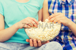 close up of kids with popcorn bowl eating