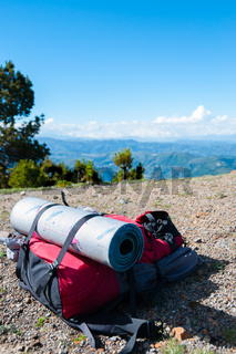Red Backpack With sleeping mat Lays on rocky ground in front mountain Tajamulco and blue sky with clouds