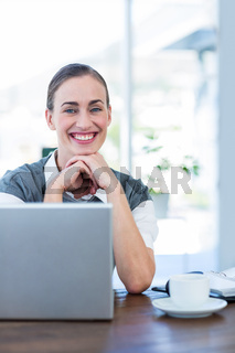 Happy businesswoman looking at camera behind laptop computer