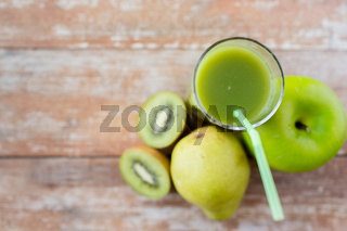 close up of fresh green juice and fruits on table