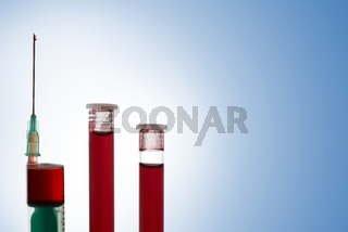 Syringe and two vials of blood on blue background