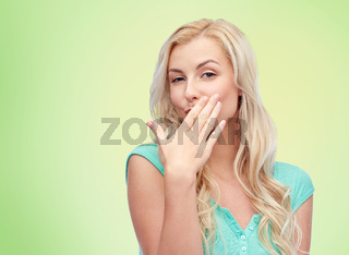 smiling young woman or teen girl covering mouth