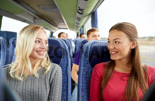 happy young women talking in travel bus