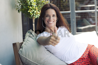 Woman giving thumb up approval hand sign gesture smiling