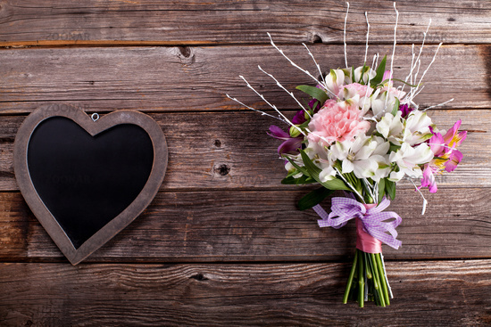 Summer bouquet from gillyflowers and alstroemeria on old wooden background with wooden heart