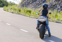 Blonde girl rides on modern motorcycle.