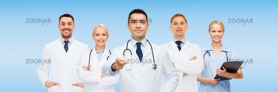 group of doctors with clipboard pointing at you