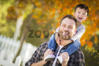 Mixed Race Boy Riding Piggyback on Shoulders of Caucasian Father