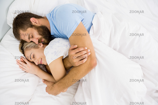 Man embracing woman while sleeping on bed