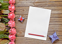 Row of pink roses, boxes and pencil with paper