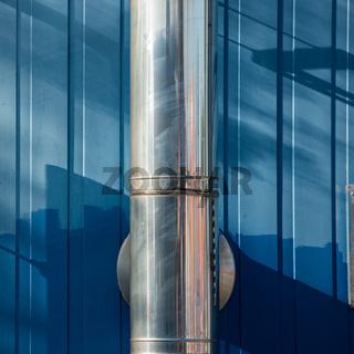 Abgasrohr vor blauer Wand