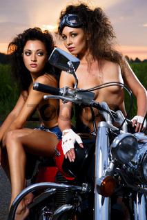 Two sexy young woman sitting on a motorcycle outdoors